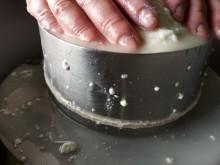 As mãos da queijeira prensam o leite de cabra coalhado.