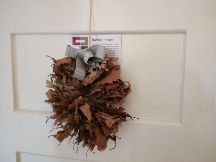 Coroa feita com folhas secas pendurada na porta do quarto Bardo da Casa Cerro da Correia.