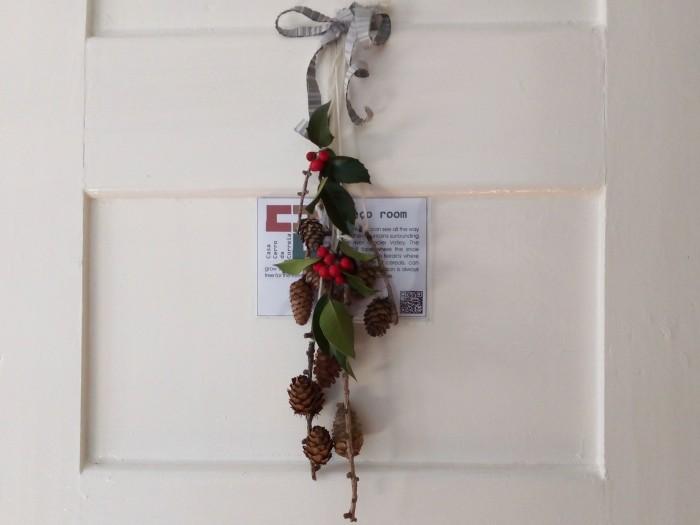 Coroa feita com pinhas e azevinho pendurada na porta do quarto Cabeço da Casa Cerro da Correia.
